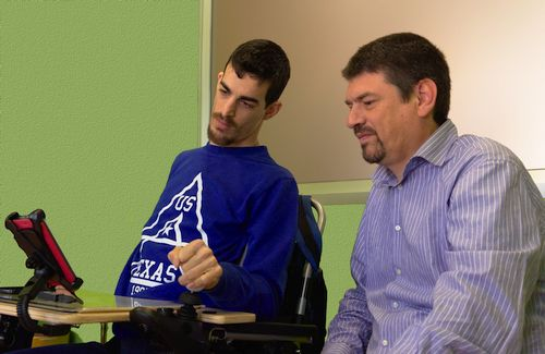 person with cerebral palsy using a mobile device with a joystick and cesar observing